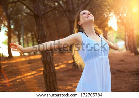 Young happy woman stretching on forest background. - stock photo