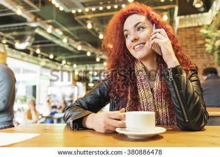 Young happy woman talking on the phone in coffee shop. - stock photo