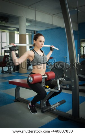 Young happy woman training in the gym