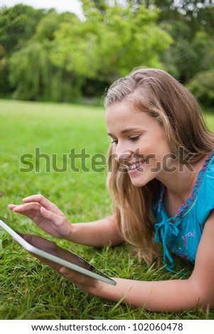 Young happy woman using her tablet pc while lying on the grass in a public garden - stock photo