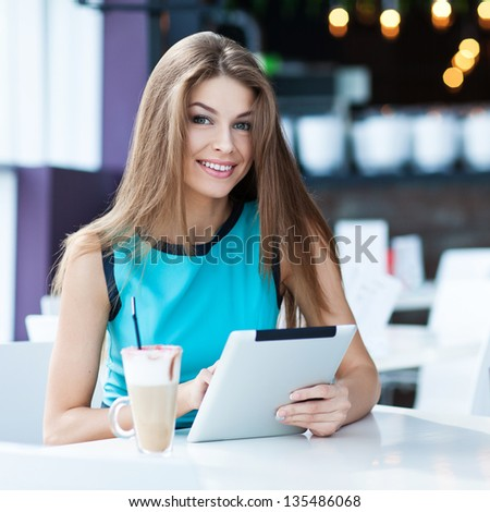 young happy woman using tablet computer in a cafe - stock photo