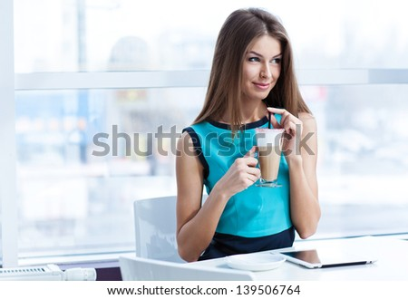 young happy woman using tablet computer in a cafe