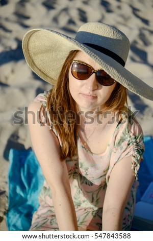 Young happy woman wearing dress on the beach. Summer time