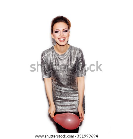 Young happy woman wearing silver dress and holding pink balloon on white background not isolated - stock photo
