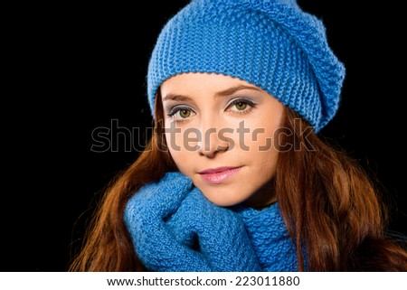 Young happy woman wearing winter cloth, isolated over black - stock photo