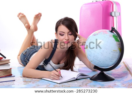 Young happy woman with a suitcase lying on the plan maps trips. Concept vacation.