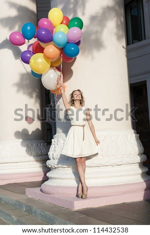 Young happy woman with colorful latex balloons keeping her dress, urban scene, outdoors - stock photo