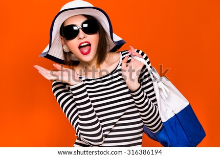 Young happy woman, with dark hair, wearing in striped blouse, black sunglasses and white hat, is standing with white and blue bag, on orange background, in studio, waist up