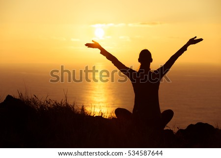 Young happy woman with her arms in the air watching the beautiful sunset.