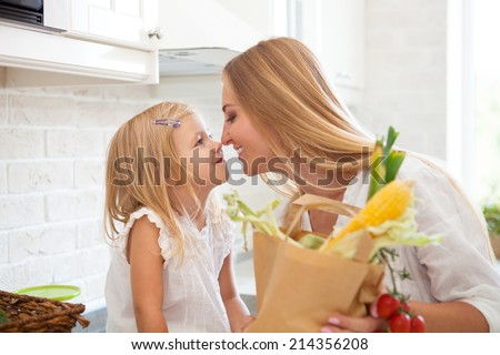 Young happy woman with her daughter cooking in a modern kitchen setting - stock photo