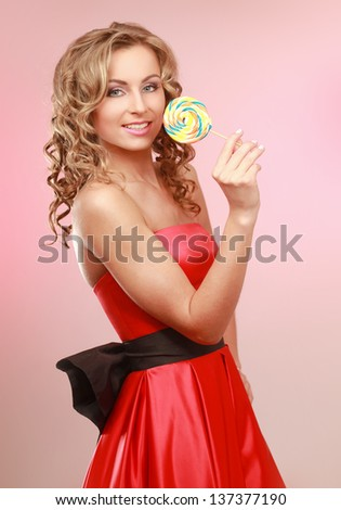 young happy woman with lollipop, isolated on pink background - stock photo