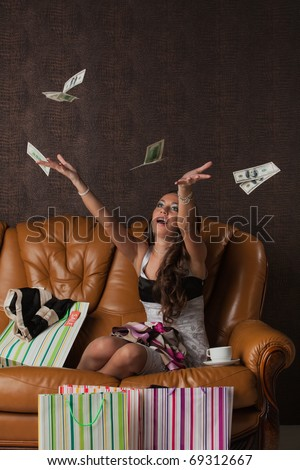 Young happy woman with  money and shopping bags sit on leather sofa at home. Sale. - stock photo