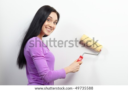 Young happy woman with paint roller - stock photo