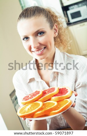 Young happy woman with plate of oranges and grapefruit