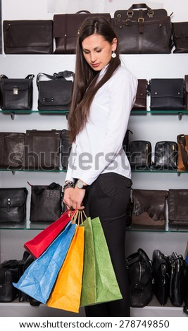 Young happy woman with shopping bags in the mall