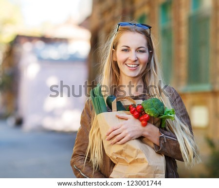 Young happy woman with shopping bags outdoors - stock photo