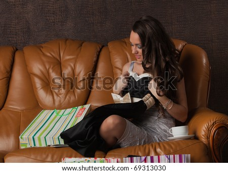 Young happy woman with shopping bags sits on leather sofa at home. Sale. - stock photo