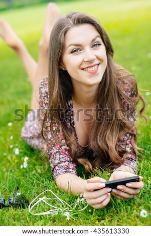 Young happy woman with smartphone lying on the grass in the park - stock photo