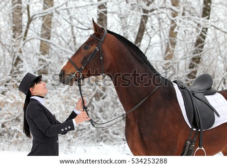 Young happy womane with horses walking in winter day