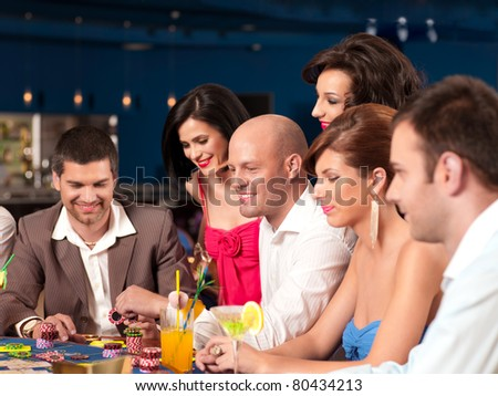 young happy women and men playing blackjack