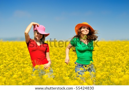 young happy women on blooming rapeseed field in summer - stock photo