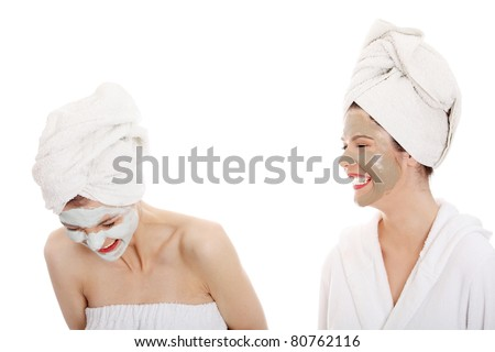 Young happy women with facial clay mask , isolated on white - stock photo