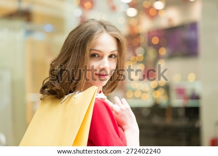 Young. Happy young woman shopping spree standing near window. Portrait of happy young woman with shopping bags on the mall alley - stock photo