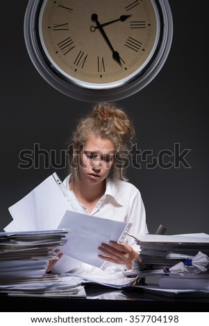 Young hard-working woman is loaded with paperwork - stock photo