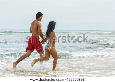 Young Hawaiian couple jogging on the beach
