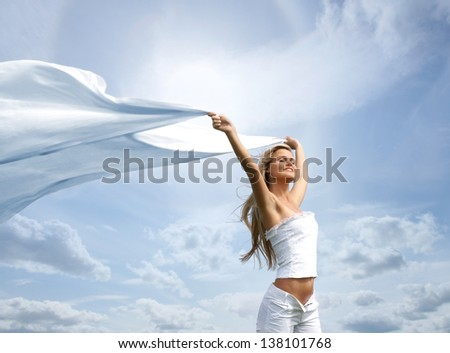 Young, healthy and beautiful woman over the sky background - stock photo