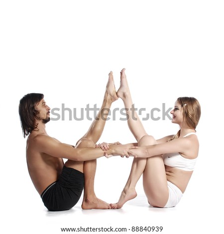 Young healthy couple in yoga position on white background