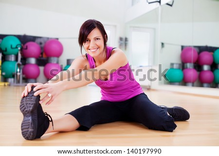 Young healthy female stretching holding her foot inside the gym - stock photo