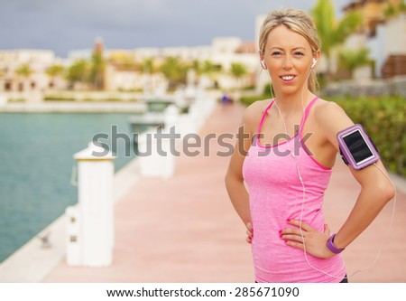 Young healthy fit woman with smartphone holder on her arm - stock photo