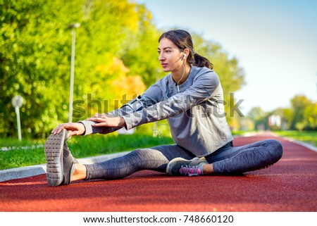 Young Healthy fitness woman runner stretching legs before running