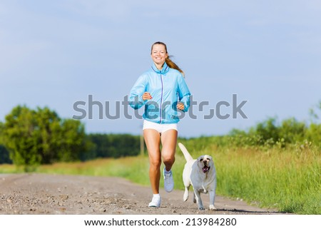 Young healthy girl running outdoor with her dog