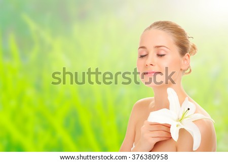 Young healthy girl with flower on yellow and green spring background - stock photo