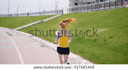 Young healthy lifestyle woman running at sunrise road. Girl running at asphalt road. Girl running in yellow sports shirt and black shorts - stock photo