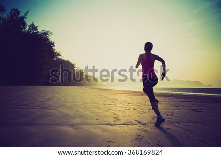 young healthy lifestyle woman running on sunrise beach