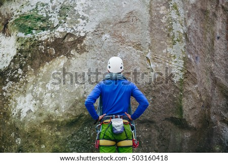 Young healthy man wearing in climbing equipment with rope standing in front of a stone rock and preparing to climb