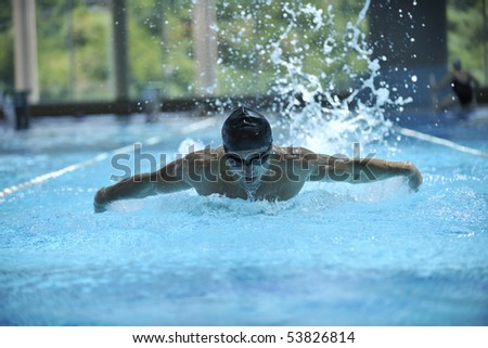 young healthy man with muscular body swims in swimming pool and representing healthy and recreation concept - stock photo