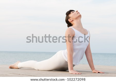 Young healthy woman doing yoga position at sea: Cobra pose - stock photo