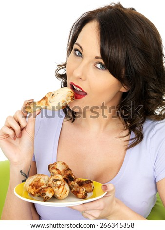 Young Healthy Woman Eating Cold Cooked Chicken Legs - stock photo