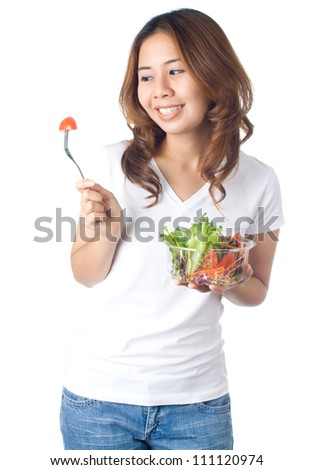 Young healthy woman holding vegetable salad in plastic bowl and looking to the pieces of tomato on fork on white background