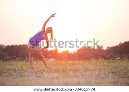 Young healthy woman is doing stretching exercise relaxing and warm up after jogging and running in the nature during beautiful sunset. - stock photo