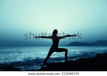 Young healthy woman practicing yoga fitness exercise on the beach at sunset. Healthy lifestyle concept. Copy space text.