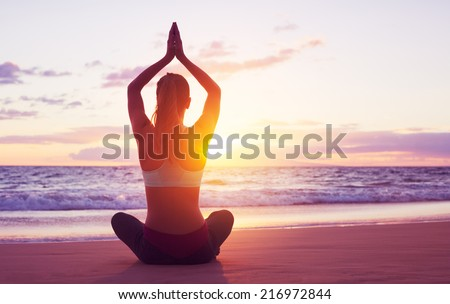 Young healthy woman practicing yoga on the beach at sunset - stock photo