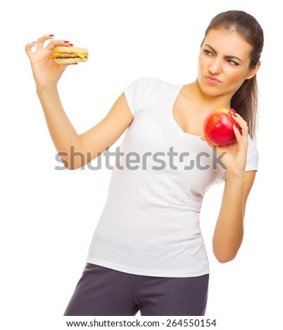Young healthy woman with apple and hamburger isolated - stock photo