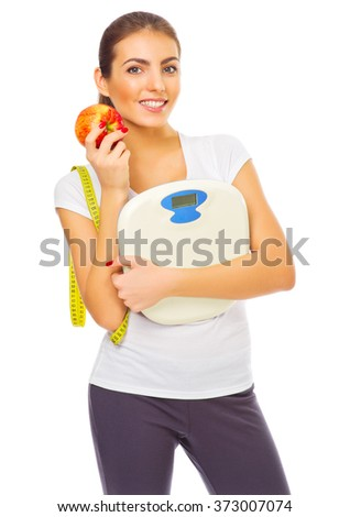 Young healthy woman with apple and scales isolated - stock photo