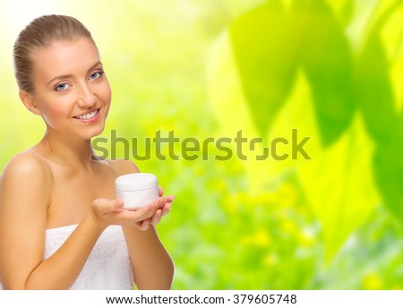 Young healthy woman with body cream on spring background