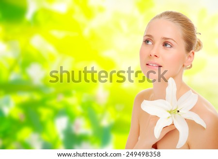 Young healthy woman with flower on spring floral background - stock photo